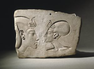 Head of a king (left), maybe Akhenaten with a khat headdress and a royal uraeus. With him is Queen Nefertiti wearing cap crown with a uraeus too.